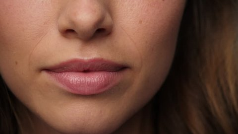 Woman putting finger to lips in close up