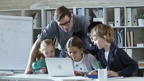Tracking shot of young teacher helping four primary school children do task on laptop computer together