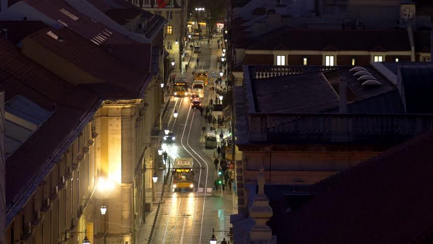 Lisbon, Portugal. Bridge, harbor and traffic on Rua do Arsenal in sunset lights. Tilt shot