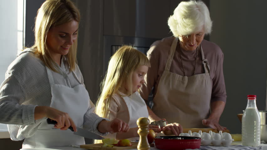 Mother, little daughter and grandmother cooking together apple pie in the kitchen for family dinner | Shutterstock HD Video #1008275452