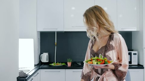good morning, happy woman in silk nightdress holds dish with fresh vegetables salad and drinks water from glass