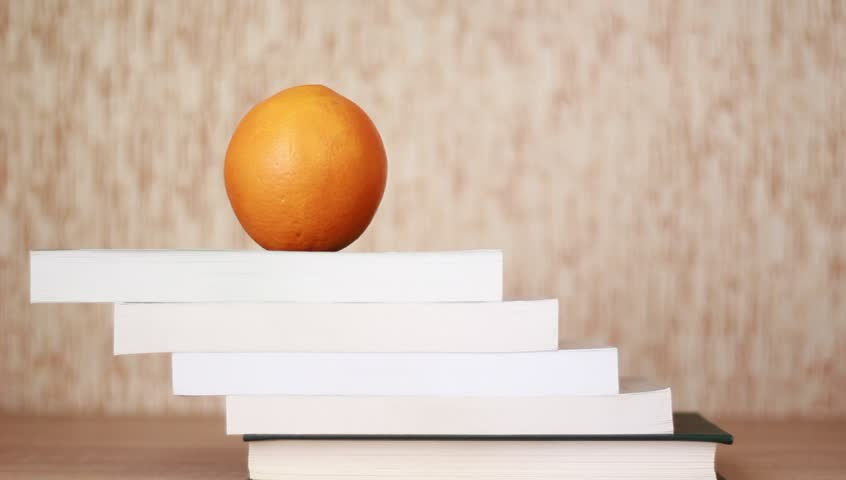 Hand going up book stairs and taking orange