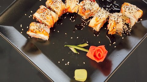 Sushi on a black plate decorated with roses in Ginger