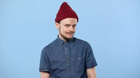 Portrait of caucasian guy with curly mustache wearing hat expressing approval and nodding positively, isolated over blue background. Concept of emotions