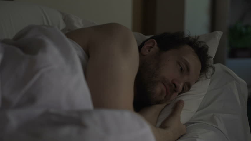 Annoyed man tossing and turning in bed unable to fall asleep, noisy neighbors