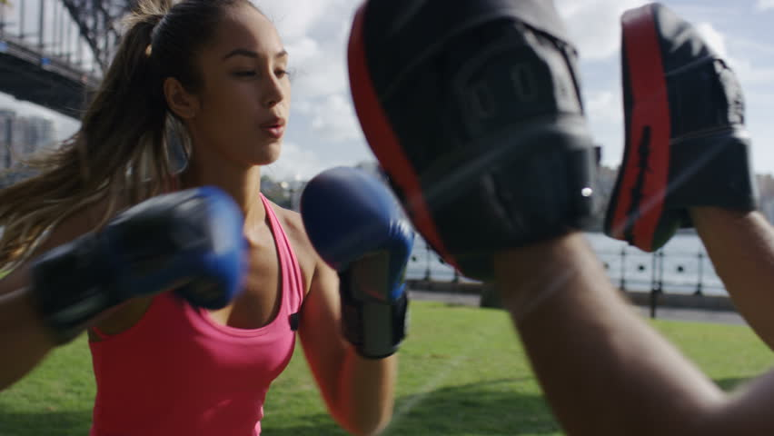 Young athletic female doing boxing training with personal trainer, in slow motion