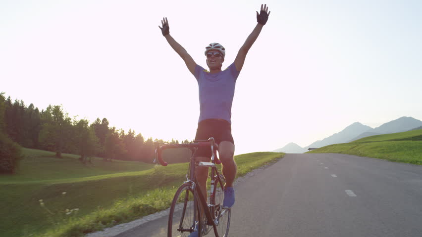 LENS FLARE: Professional biker raising his arms victoriously after winning race. Cheerful biking athlete celebrates victory in quiet countryside. Pro cyclist cheerfully rides road bike with no hands.