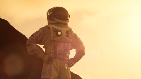 Astronaut Looking Around while Standing on the Mars/ Red Planet, Stands with Arms Akimbo. In the Background His Base/ Research Station. Space Exploration, Colonization Theme. Shot on RED EPIC-W 8K.