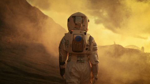 Following Shot of Female Astronaut in Space Suit Confidently Walking on Mars, Turing Around and Looking into the Camera. Red Planet Covered in Gas and Smoke. Shot on RED EPIC-W 8K Helium Cinema Camera