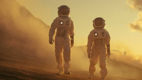 Two Astronauts in Space Suits Confidently Walking on Mars, Exploration Expedition on the Planet's Surface. Red Planet Covered in Rocks, Gas and Smoke. Humans Overcoming Difficulties. 4K UHD,