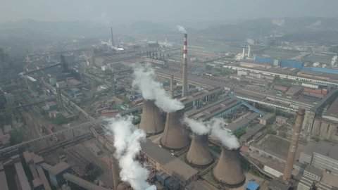 Aerial shot of polluting coal fired power reactors on the grounds of a huge steel producing factory in China. Camera tilting down halfway during the drone flight.