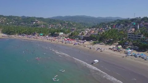 Aerial tour over the beautiful Sayulita beach on a hot and clear day with vacationers swimming in the sea and enjoying the beautiful climate of Nayarit