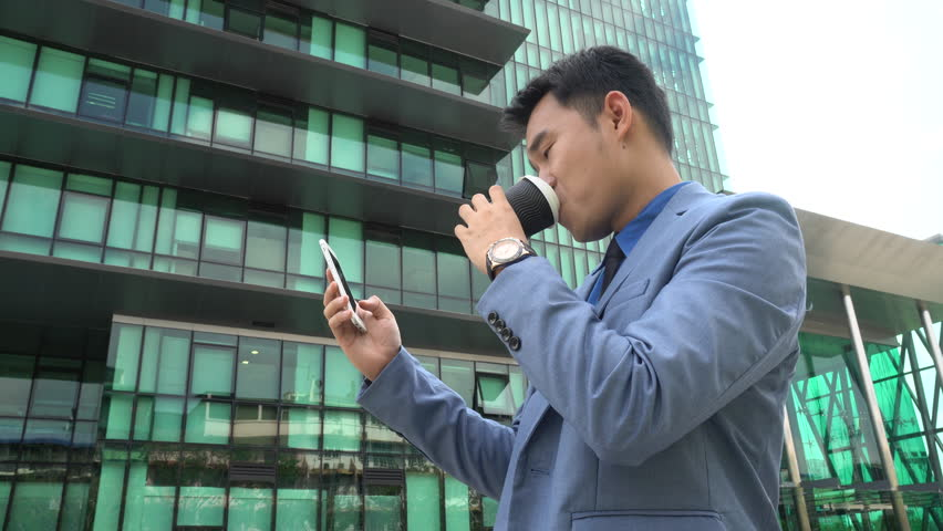 Asian young businessman hand holding morning coffee and reading phone on urban | Shutterstock HD Video #1008436732