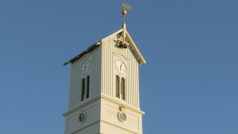 top of tower of icelandic church with clock, bells and weathercock, against clear blue sky