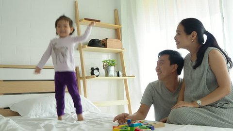 Asian family with happy time at home,daughter dancing and jumping on bed and parent sing a song.