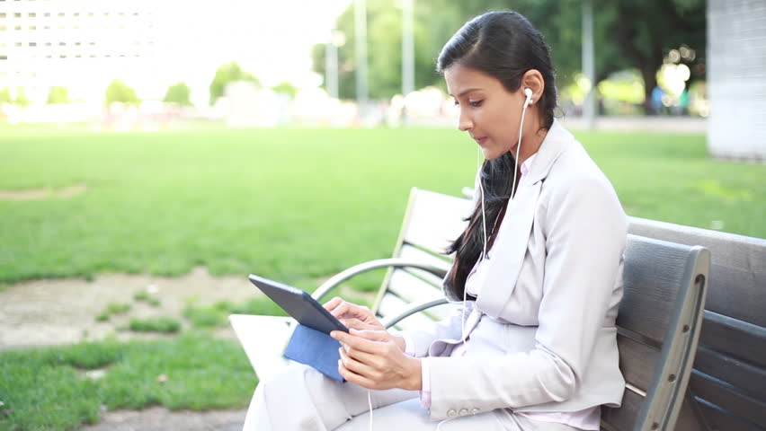 Hispanic woman reading ebook using a electronic tablet in yellow closeup portrait pretty woman in white gray suit listening to music on touch pad tablet fandeluxe Ebook collections