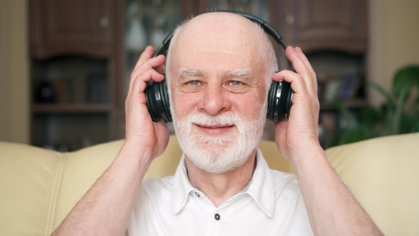 Modern senior man listening music with big black wireless headphones. Positive pensioner meloman dancing to music. Concept of technology use by older people. Active modern life after retirement