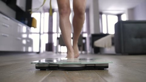 Close-up slow motion shot of woman approaching weight scale with measuring tape in hand, her legs stepping on scale, then jumping off and start dancing. Weight loss, dieting concept