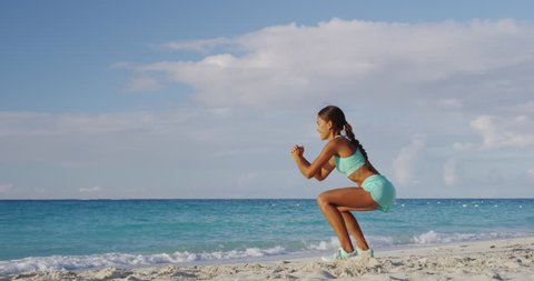 Squat pulses - Fitness young woman working out glutes with bodyweight workout doing squat pulse exercises on beach. Asian sporty girl squatting legs as part of an active and fit life.