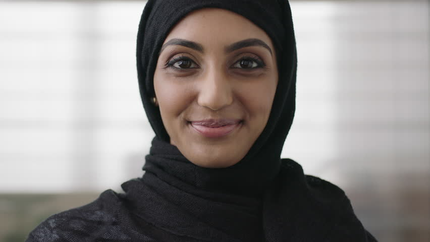 close up portrait of professional young muslim business woman looking at camera smiling happy wearing traditional headscarf in office background