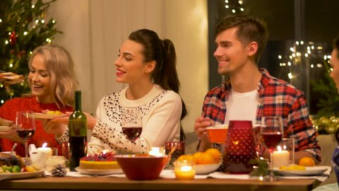 holidays and celebration concept - happy friends having christmas dinner party at home and eating