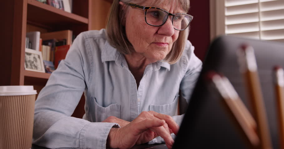 Close-up of senior woman typing on laptop alone in personal home office. Portrait of older woman using portable computer while sitting indoors in domestic setting. 4k
