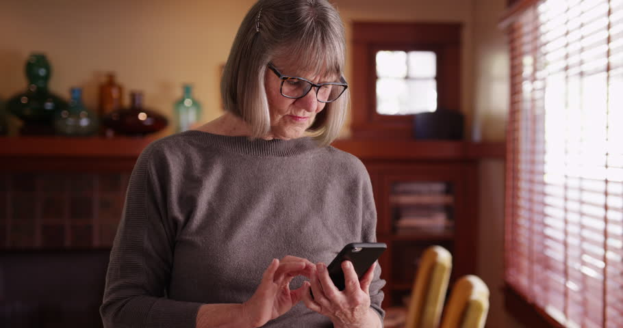 Serious senior woman using phone reading tragic news standing in living room. Somber lady reading e-mail on cell phone looking concerned in indoor setting. 4k