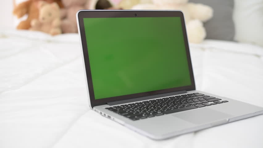 Computer laptop with green screen display on the bed. | Shutterstock HD Video #1008557782