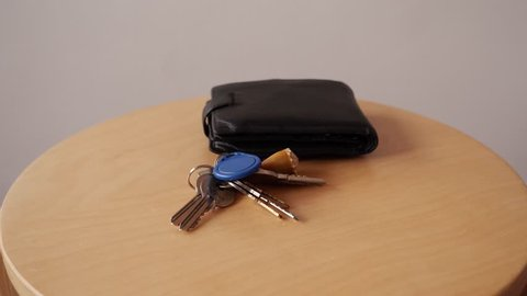 Taking Keys and wallet to little table and Taking them from table . Arriving / Leaving Home concept.Time lapse.