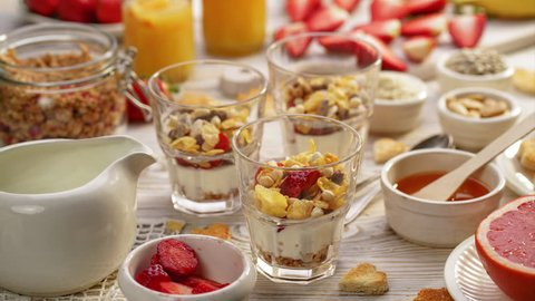 Natural yogurt with fresh fresh strawberries, granola, honey, nuts and seeds in a glass dishes. Delicious breakfast or dessert. Healthy eating concept. Stop motion animation.
