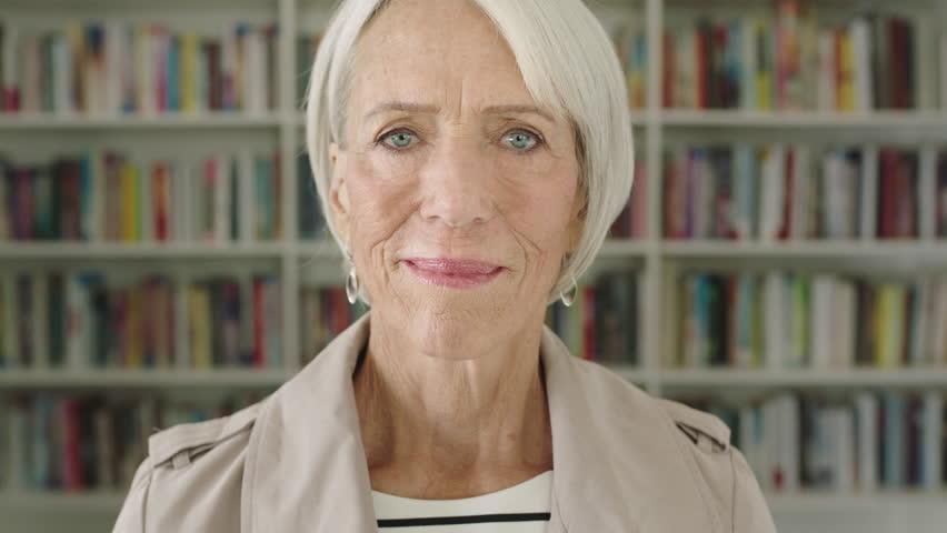 Portrait elderly woman student smiling bookshelf library university | Shutterstock HD Video #1008611332
