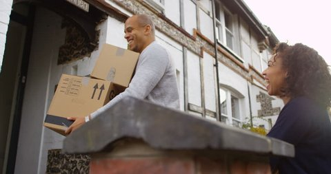 4K Smiling couple moving house, carrying boxes into their new home. Slow motion.