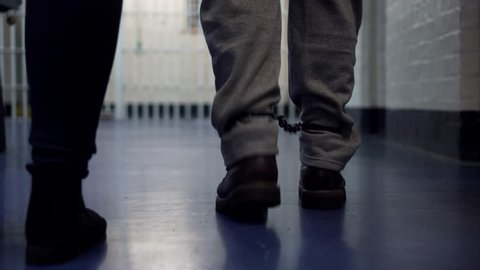 Prison Corrections Officer Guard Escorts Inmate With Handcuffs On. 4K Crime, Prisoner Incarceration.