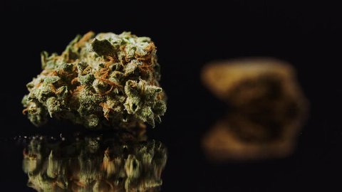 Cannabis bud on black rack focus to chunk of hash