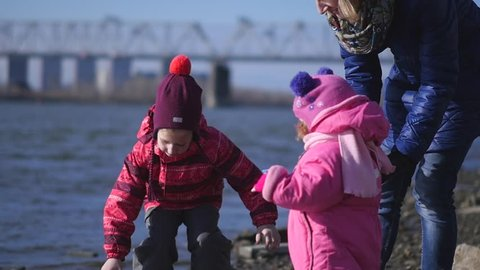A young mother and two little daughters are walking on the city embankment of the river. Slow motion