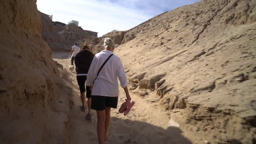 Grandmother, daughter, and grandson all walk up a sandy eroding canyon on a warm morning.