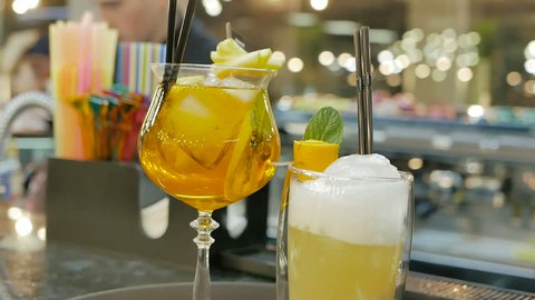 Closeup glass yellow cocktail bar stand festive background barmaid preparing drink alcohol granulated ice cold summer straw decorating