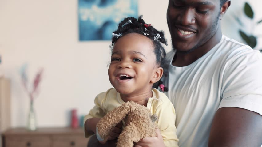 Sweet little African American baby-girl is held on her father's arms, laughs and tries to get away from his hugs. Favorite toy, positive emotions. Slow motion, close up view