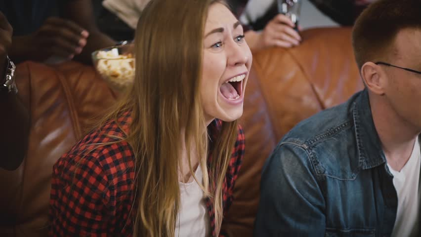 Girl watching sports on TV with friends. Slow motion. Female football fan. Emotional supporter celebrates success.