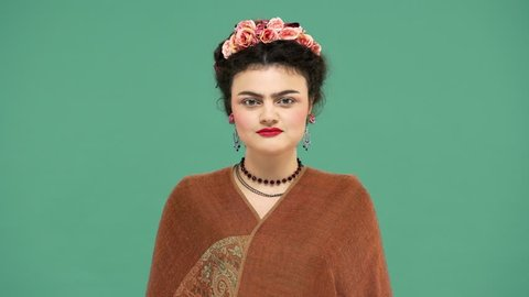 Fashion portrait of woman with thick eyebrows and red lips makeup as Frida Kahlo smiling wearing