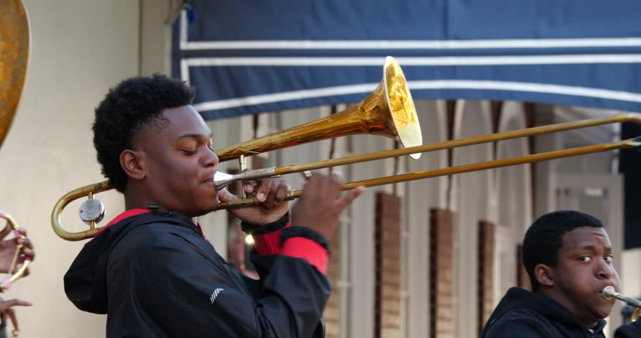 New Orleans LA Oct 2017 : Young street musician playing a trombone on the sidewalk on Bourbon St New Orleans Louisiana as part of a band performing to people passing by