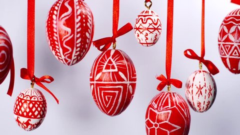 Easter red eggs with white folk pattern, hang on red ribbons with bow on white. Ukrainian traditional eggs pisanka and krashan.