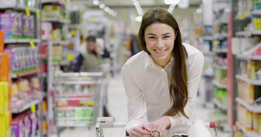 Portrait a beautiful woman, goes shopping for the house and buy products for eating, cleaning the house and products for the care of your body in a supermarket. Concept of: shopping, family and home. | Shutterstock HD Video #1008741692