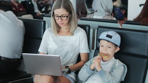 Young mum working on laptop on airport with child enjoying lollipop. Busy businesswoman, freelancer using computer in trip, writting email. Business, freelance, online education, trading concept