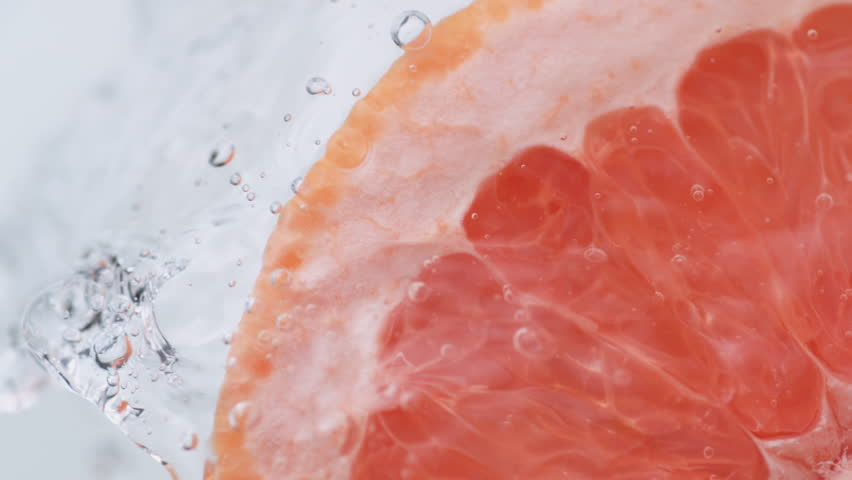Halved pink grapefruit falling in water. Shot with high speed camera, phantom flex 4K. Slow Motion.