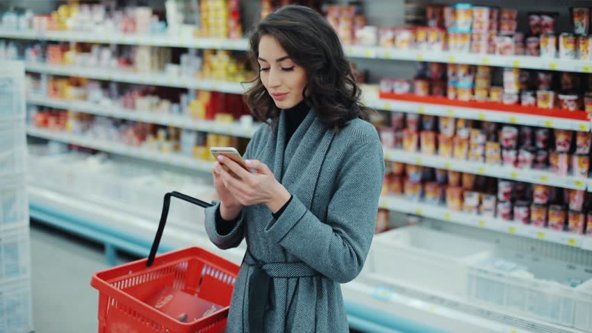 Brunette young woman walk checking to do list on phone in supermarket smiling thinking shopping internet buy technology hypermarket shop mall smartphone grocery market girl food customer slow motion