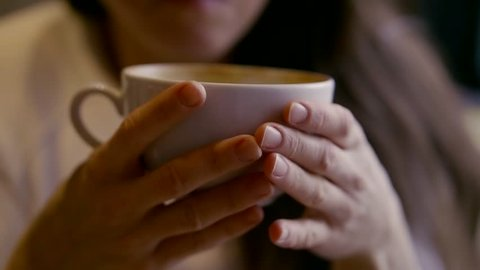 middle-aged woman sitting in a cafe with a Cup of tea or coffee and swallowing. Close-up of hands with a Cup