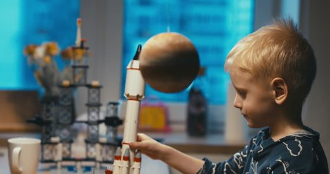 Little kid boy playing with toy space rocket, flying among planets. 4K UHD