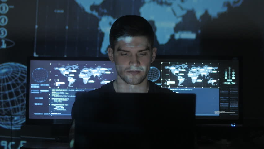 Male hacker programmer working at computer while blue code characters reflect on his face in cyber security center filled with display screens. | Shutterstock HD Video #1008780362
