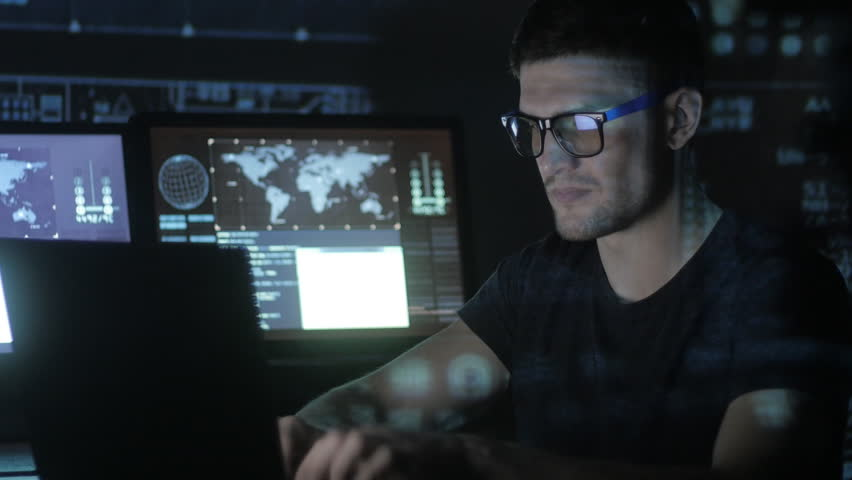 Hacker programmer in glasses is working on computer while blue binary code characters reflect on his face in cyber security center filled with display screens. | Shutterstock HD Video #1008780392